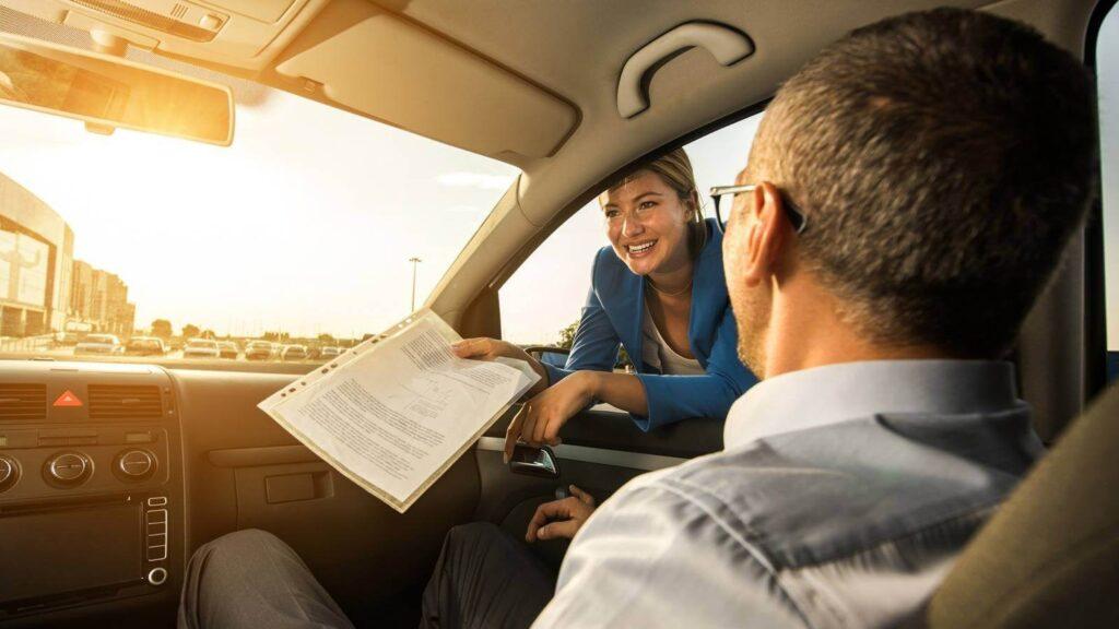 vendedora conversando com um homem que está dentro do carro  post como vender carros em 2019