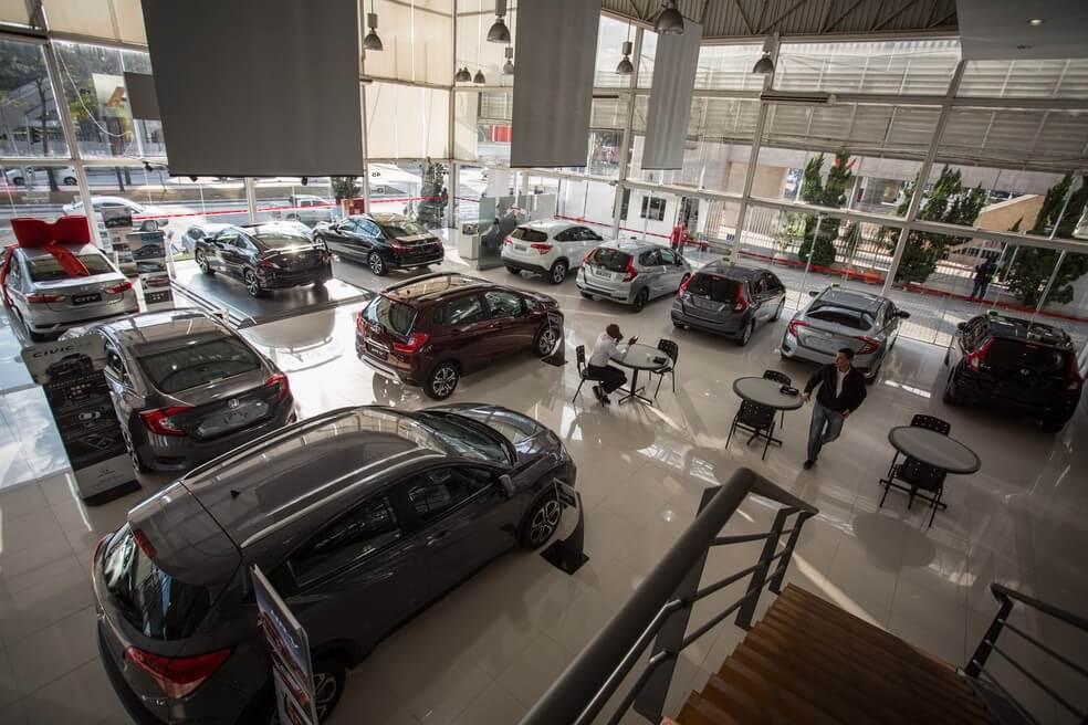 reabertura de concessionária de veículos. carros distribuídos no showroom da loja, homem atendendo telefone em uma mesa e outro homem aguardando falar com vendedor.