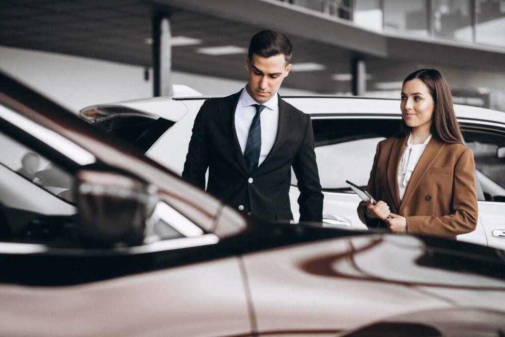 Dois profissionais de concessionários, um homem e uma mulher. Os dois estão em pé em frente a um carro observando-o. Eles usam terno e a mulher segura uma prancheta.