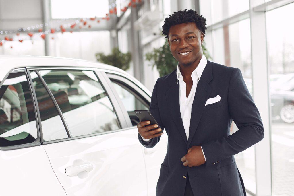 Homem de terno ao lado de um carro. Ele sorri e segura um celular enquanto desabotoa o blazer.