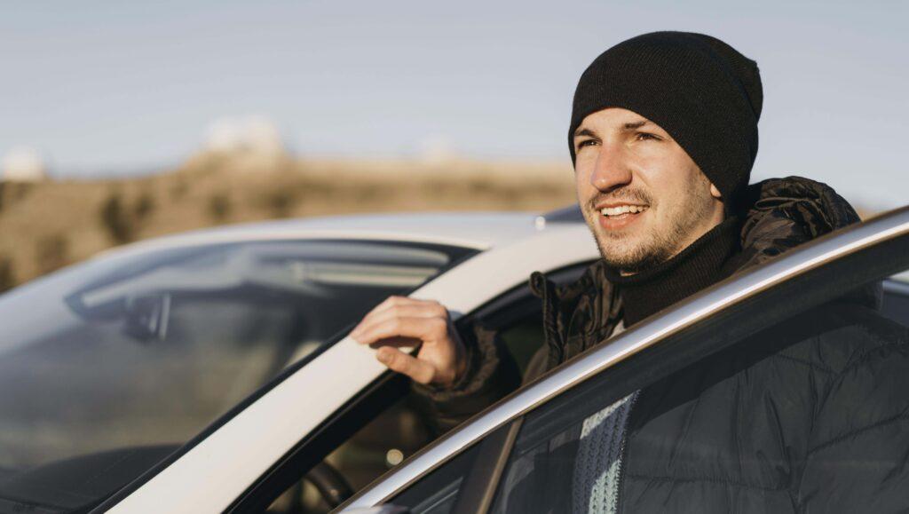 Homem vestindo gorro e roupa de frio parado ao lado de um carro com a porta aberta.