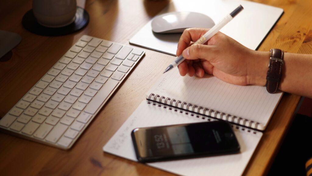"""Mesa de escritório com os seguintes objetos sobre ela: teclado de computador, mouse, caderno e celular. Vemos, ainda a mão de uma pessoa segurando uma caneta sugerindo o tema """"textos para vender carros""""."""