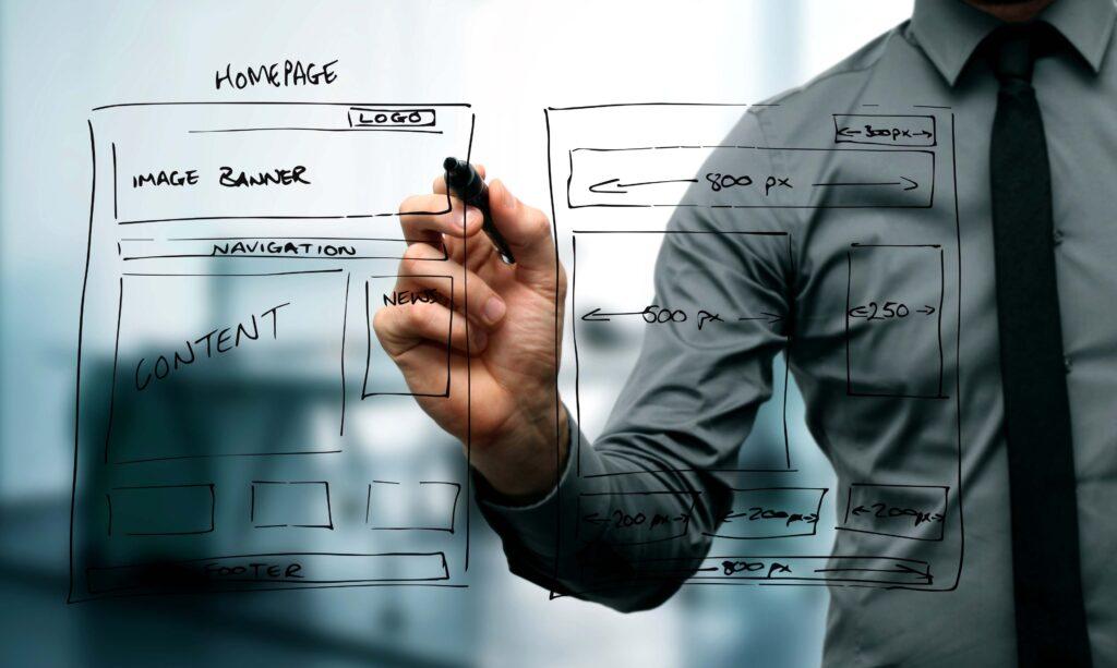 Homem desenhando em uma lousa transparente. Ele desenha a estrutura de um site mostrando graficamente onde ficam título, conteúdos e imagens.