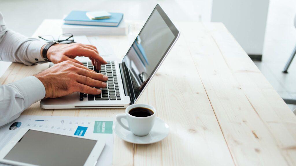 Homem mexendo em um computador sobre a mesa. Ao lado dele há uma xícara de café, papeis e livros.