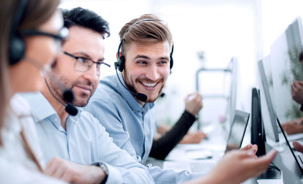 Dois homens e uma mulher com fones de ouvido atendendo clientes e sorrindo,