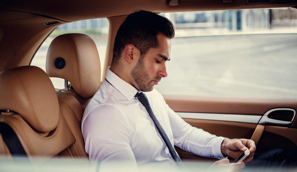 Homem sentado dentro de um carro segurando um celular.