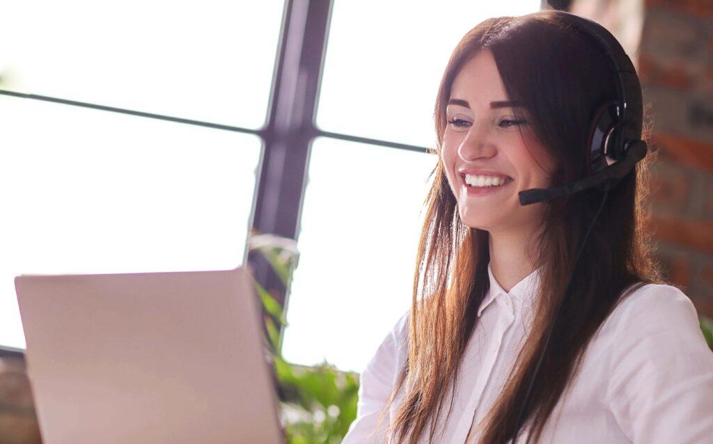 Mulher trabalhando em frente a um computador atendendo clientes. Ela usa um headphone com microfone.