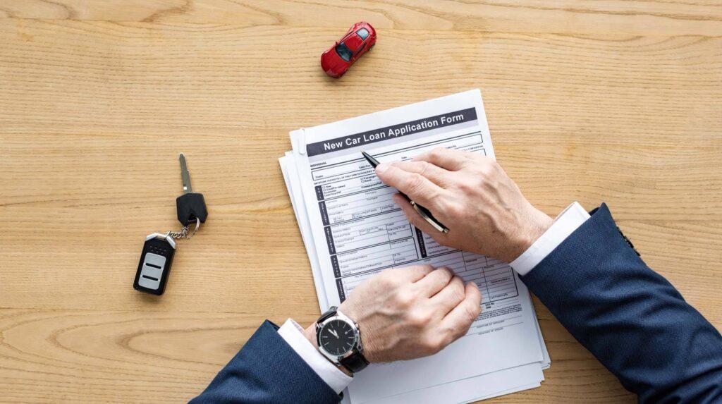 Homem de terno preenchendo um formulário para compra de carro. Sobre a mesa há um chave de carro e um carrinho de brinquedo.