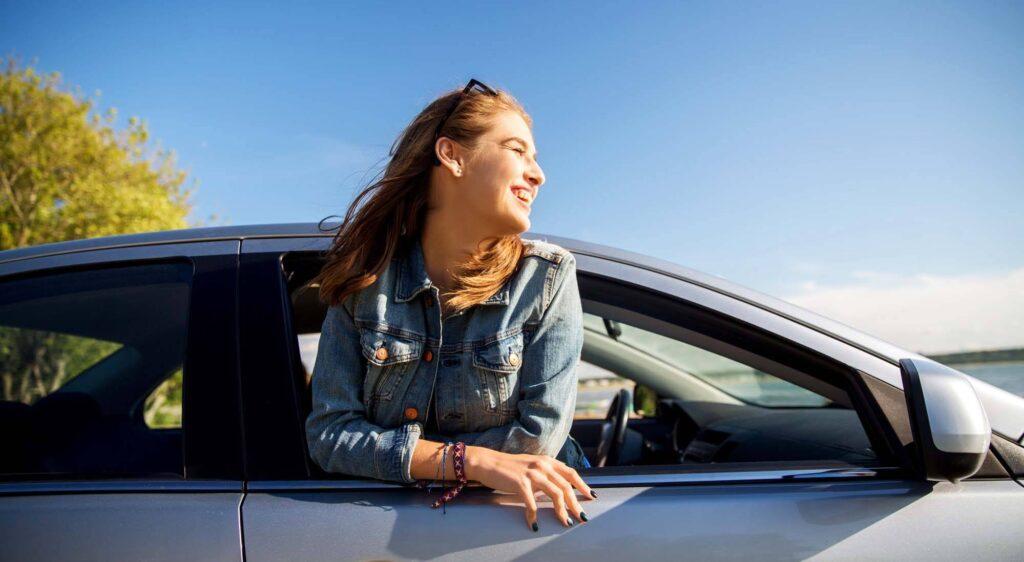 Moça sorrindo e apoiada na janela de um carro. Do lado de fora, vemos o céu azul.