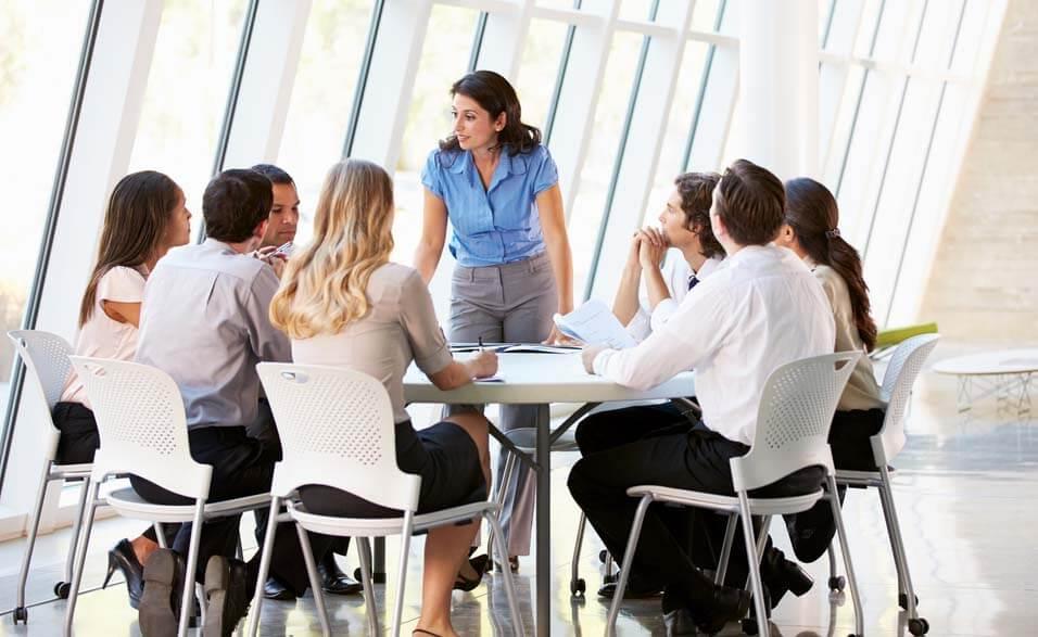 Grupo de pessoas sentada ao redor de uma mesa redonda com papeis e caneta nas mãos. Eles estão atentos a uma mulher que está de pé conversando come eles.